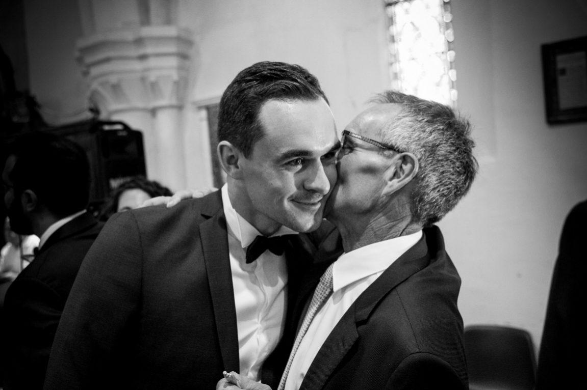 Reportage photos mariage Neufchateau Vosges- Photographe Nancy Meurthe et Moselle- le papa embrasse son fils dans l'église -www.gregory clement.fr